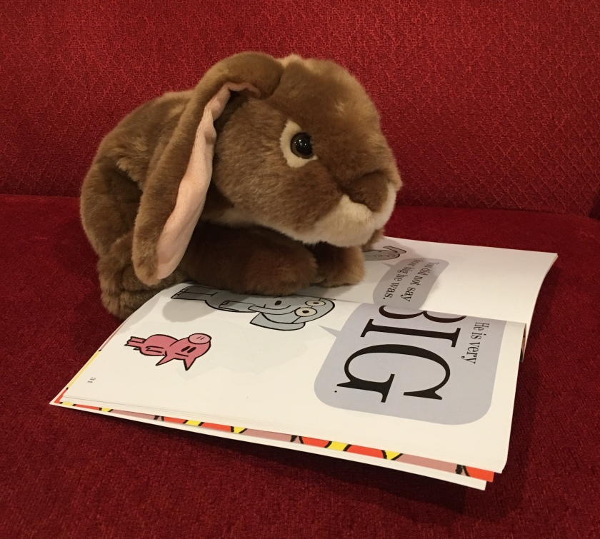 Caramel is reading the page where Gerald is telling Piggie that the big guy is really big.