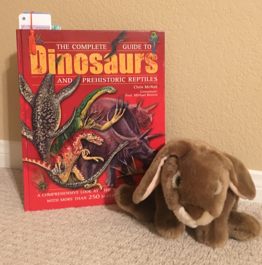 Caramel loves reading and looking at the many many pictures in The Complete Guide to Dinosaurs and Prehistoric Reptiles.