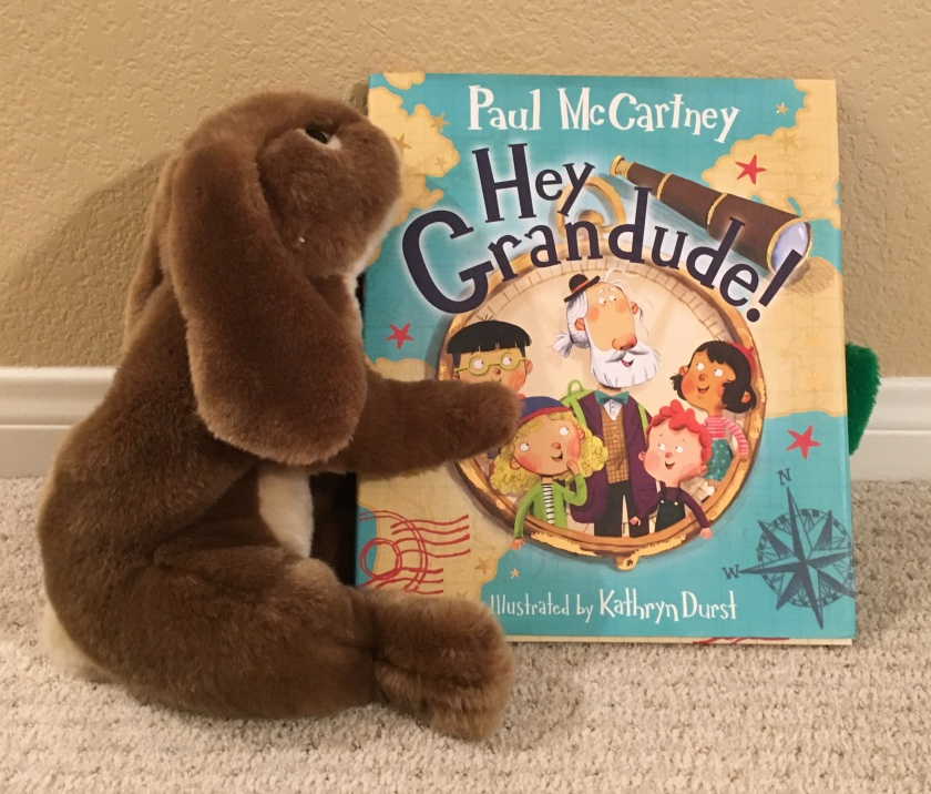 As Caramel displays Hey Grandude! written by Paul McCartney and illustrated by Kathryn Durst, a green friend is hiding in the background. Can you see him?