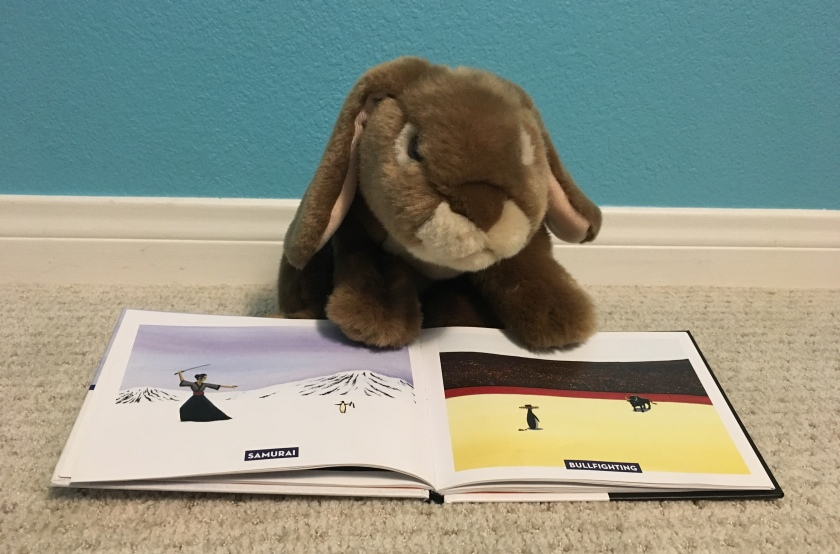 Caramel is pointing at the pages of Penguins Hate Stuff where we learn that penguins hate samurai and bullfighting.
