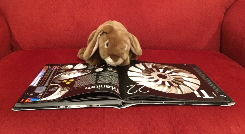 Caramel is reading about Titanium, one of his favorite elements, in  The Elements: A Visual Exploration of Every Known Atom in the Universe by Theodore Gray.