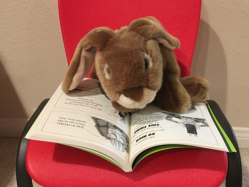 Caramel is reading The Bad Guys in Mission Unpluckable by Aaron Blabey.