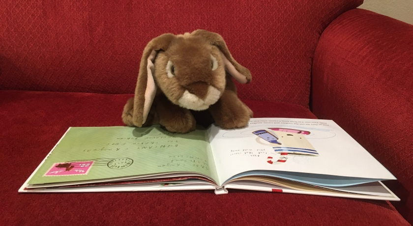 Caramel is reading The Crayons' Christmas, written by Drew Daywalt and illustrated by Oliver Jeffers.