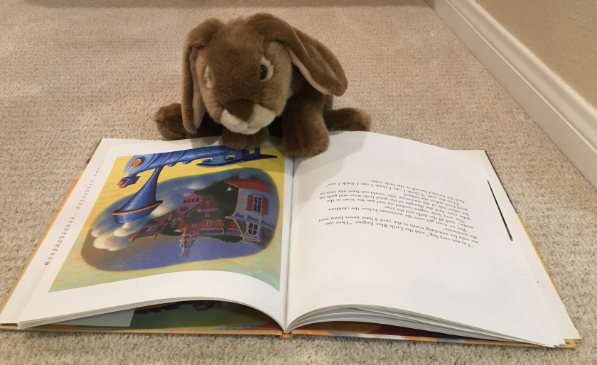 Caramel is reading The Little Engine That Could, by Watty Piper, with new art by Loren Long.