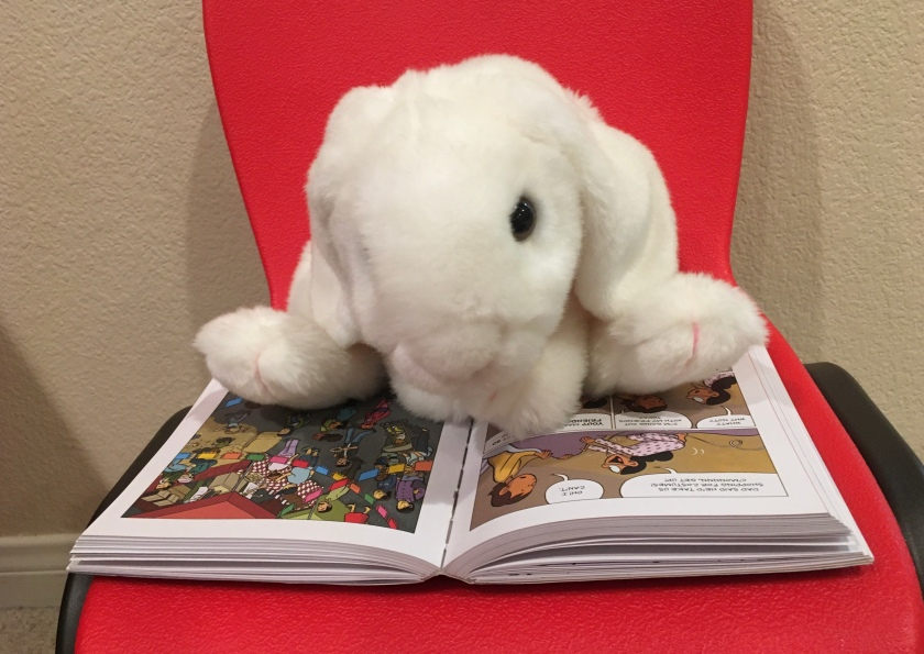 Marshmallow is reading Ghosts by Raina Telgemeier.