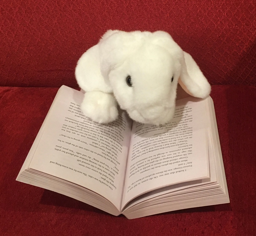 Marshmallow is reading Poached by Stuart Gibbs.