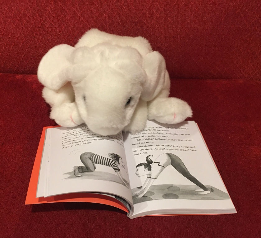 Marshmallow is pointing to the page in Ivy and Bean: One Big Happy Family by Annie Barrows and Sophia Blackhall (Book 11 of the Ivy + Bean Series) where Bean is interrupting her sister Nancy's yoga session.