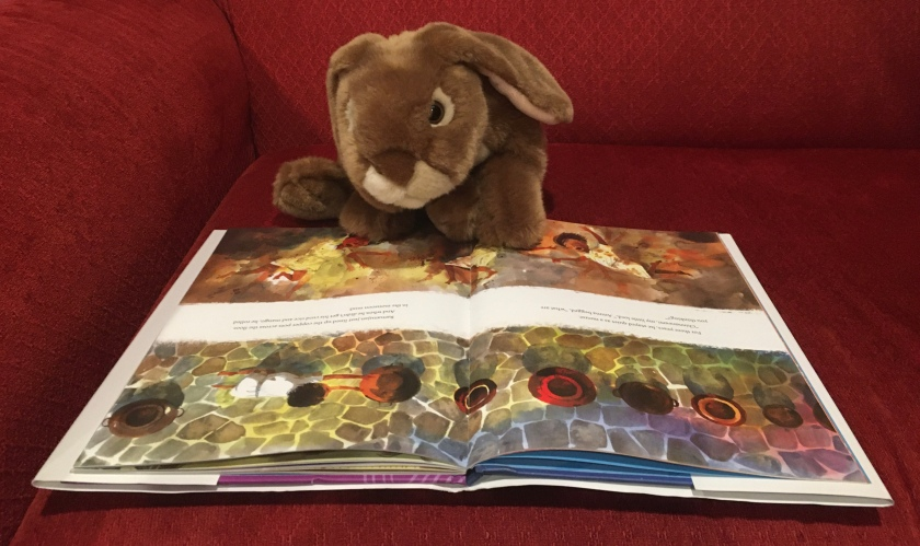 "Caramel is reading The Boy Who Dreamed of Infinity, written by Amy Alznauer and illustrated by Daniel Miyares. These pages are about when Ramanujan as a little boy was not yet speaking. Instead, he ""just lined up the copper pots across the floor. And when he didn't get his curd rice and mango, he rolled in the monsoon mud."""