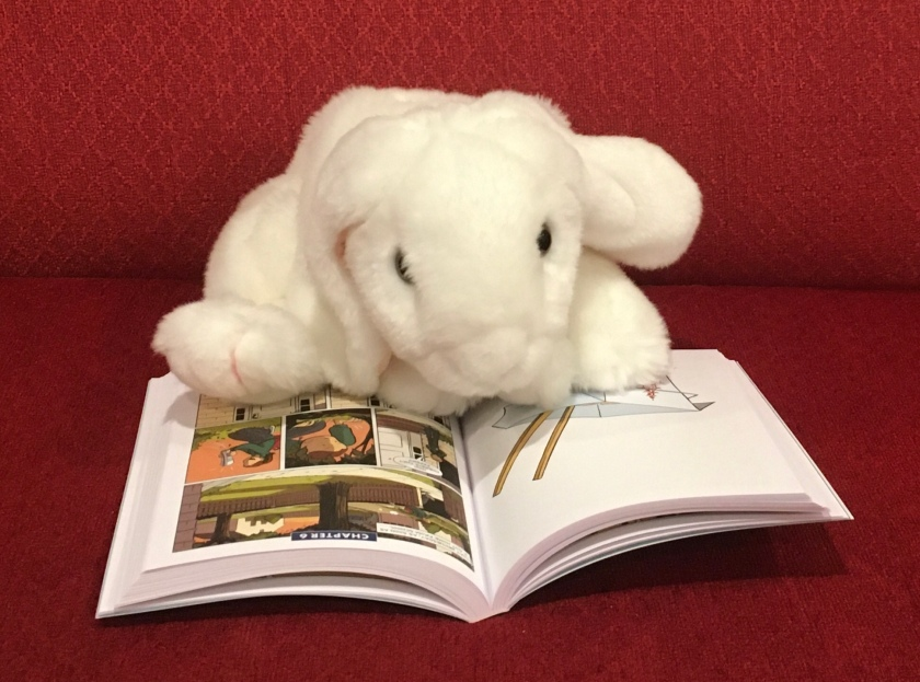 Marshmallow is reading Kristy's Great Idea (The Baby-Sitters Club Graphic Novels #1) by Ann M. Martin and Raina Telgemeier.