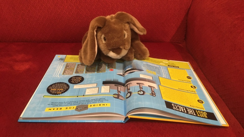 "Caramel is reading ""Caught in the tractor!"" in How Things Work by T. J. Resler."