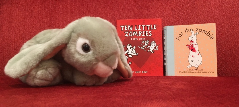 Sprinkles poses with Ten Little Zombies: A Love Story by Andy Rash, and Pat the Zombie: A Cruel Spoof by Aaron Ximm and Kaveh Soofi.