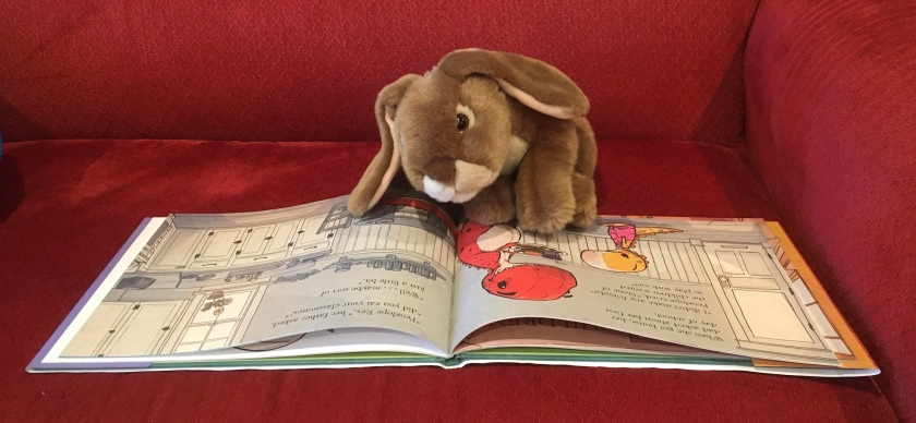 Caramel is reading We Don't Eat Our Classmates by Ryan T. Higgins.