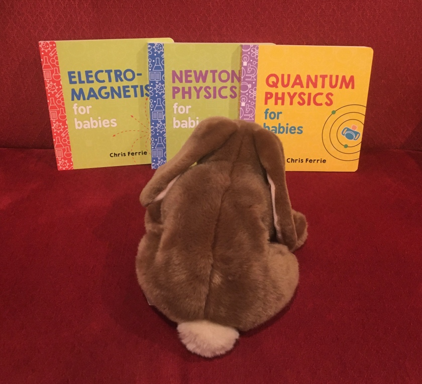 Caramel is looking at Electromagnetism for Babies, Newtonian Physics for Babies, and Quantum Physics for Babies, all written by Chris Ferrie.