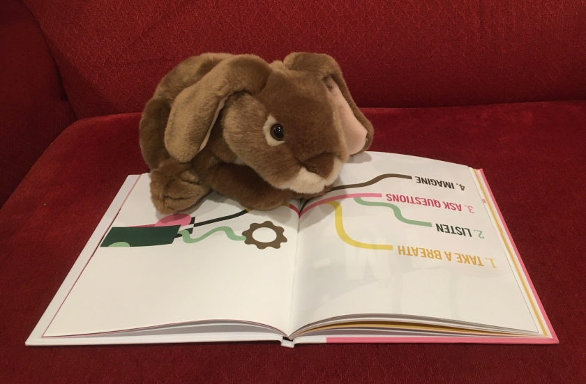 Caramel is reading A Kids Book About Empathy by Daron K. Roberts.