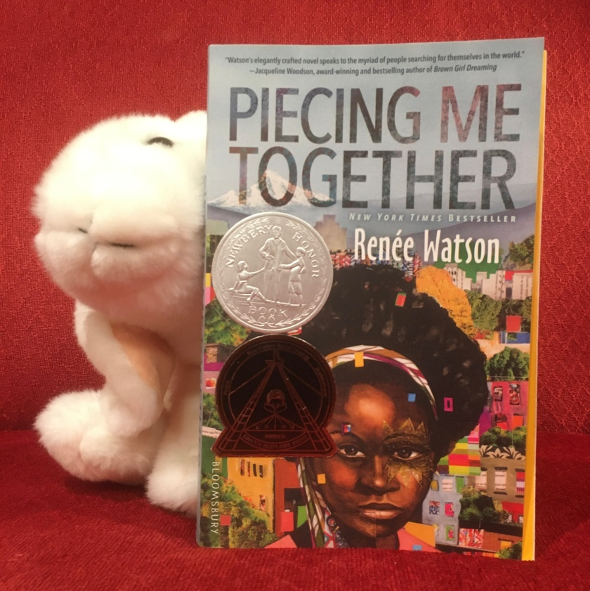 Marshmallow is reading Piecing Me Together by Renée Watson.