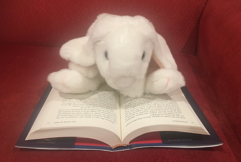 Marshmallow is reading The Tower of Nero (Book 5 of the Trials of Apollo Series) by Rick Riordan.