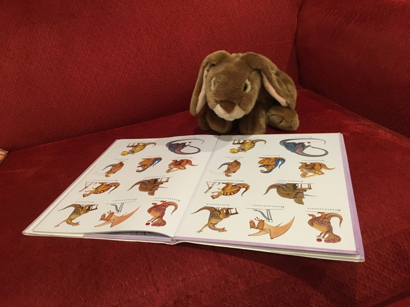 Caramel is looking at the full cast of How Do Dinosaurs Go To School? (2007),  written by Jane Yolen and illustrated by Mark Teague.
