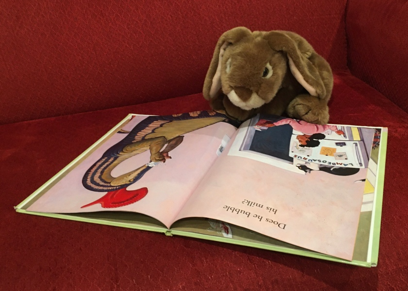 Caramel is reading How Do Dinosaurs Eat Their Food? (2005),  written by Jane Yolen and illustrated by Mark Teague.