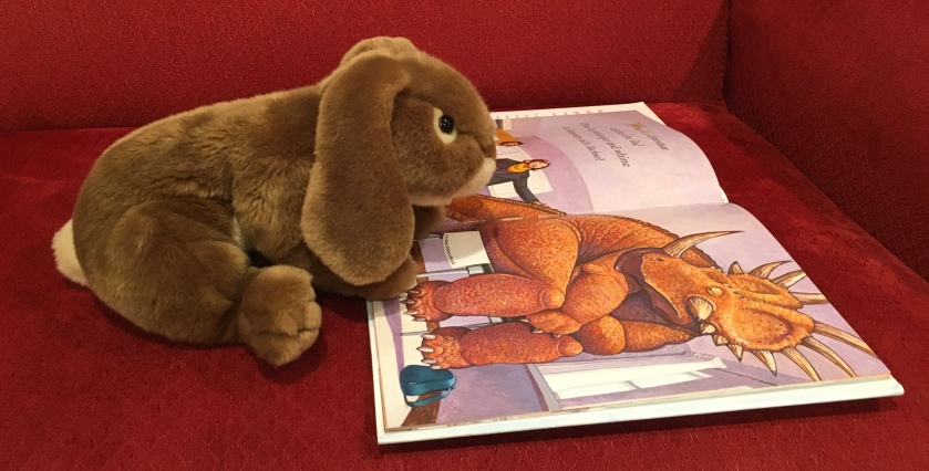 Caramel is reading How Do Dinosaurs Get Well Soon? (2003),  written by Jane Yolen and illustrated by Mark Teague.