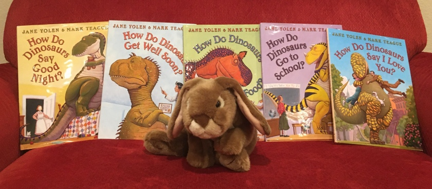 Caramel reviews How Do Dinosaurs Say Good Night? (2000), How Do Dinosaurs Get Well Soon? (2003), How Do Dinosaurs Eat Their Food? (2005), How Do Dinosaurs Go To School? (2007), and How Do Dinosaurs Say I Love You? (2009), all written by Jane Yolen and illustrated by Mark Teague.