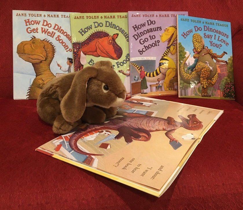 Caramel is reading How Do Dinosaurs Say Good Night? (2000),  written by Jane Yolen and illustrated by Mark Teague.