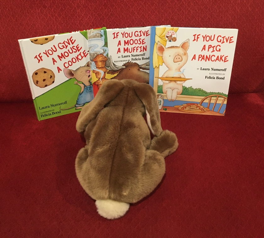 Caramel is looking at If You Give a Mouse a Cookie (1985), If You Give a Moose a Muffin (1991), and If You Give a Pig a Pancake (1998), all written by Laura Numeroff and illustrated by Felicia Bond.