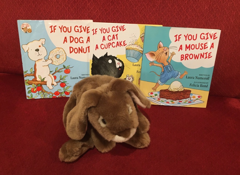 Caramel is showing the readers If You Give a Cat a Cupcake (2008), If You Give a Dog a Donut (2011), and If You Give a Mouse a Brownie (2016), all written by Laura Numeroff and illustrated by Felicia Bond.