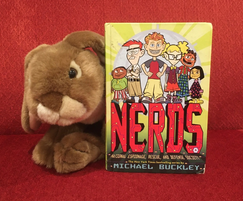 Caramel reviews N.E.R.D.S.: National Espionage, Rescue, and Defense Society, by Michael Buckley.